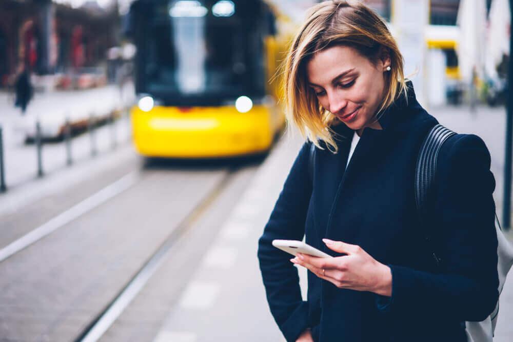 Woman looking at phone at tram station