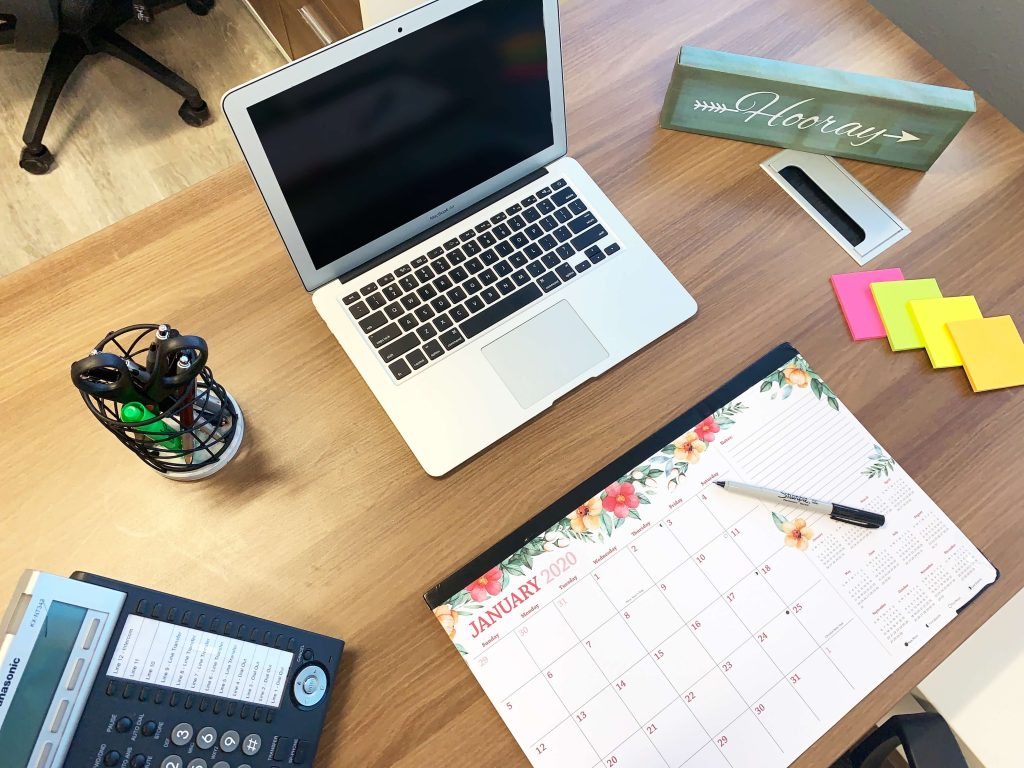 Laptop on desk with calendar in front of it