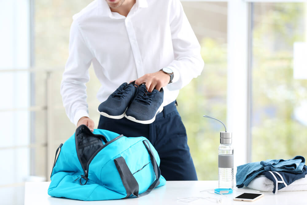 Businessman putting gym shoes in bag