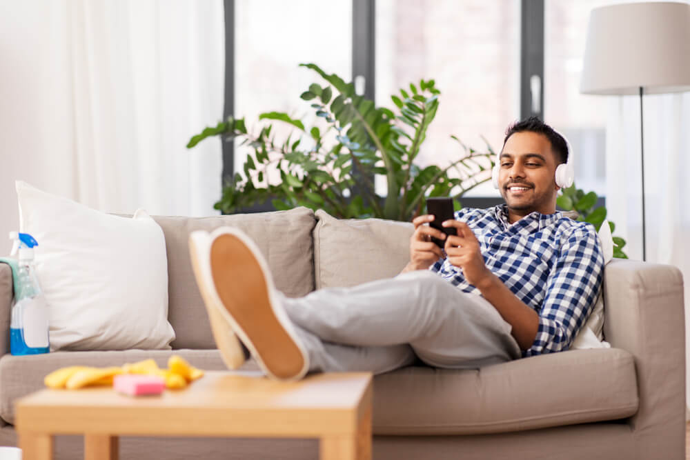 Man procrastinating by playing on phone