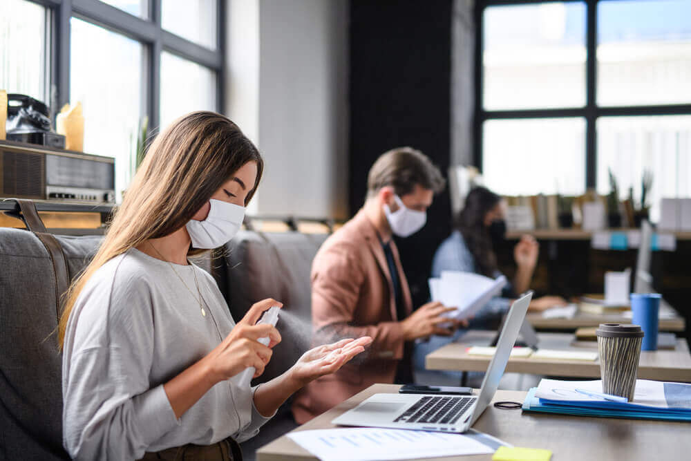 Woman in office with face mask and hand sanitizer