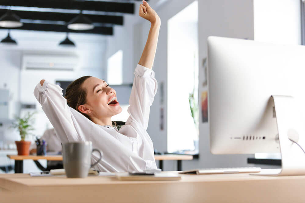 Woman smiling with arm stretched at desk at work
