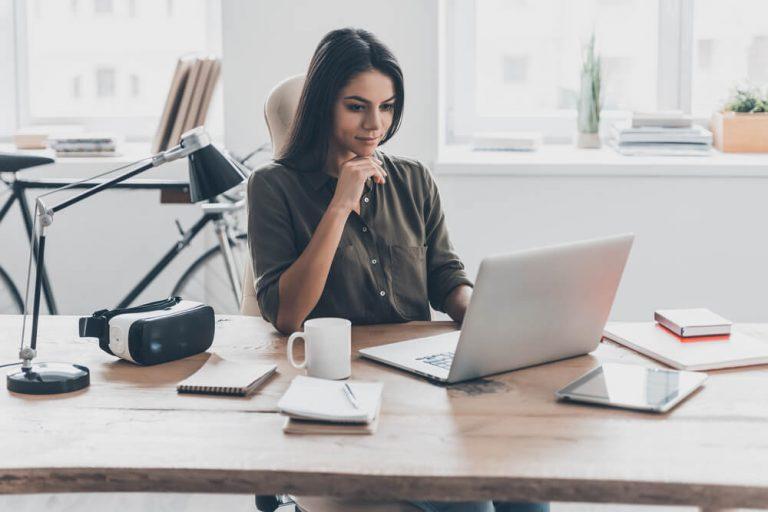 Woman at desk looking at laptop