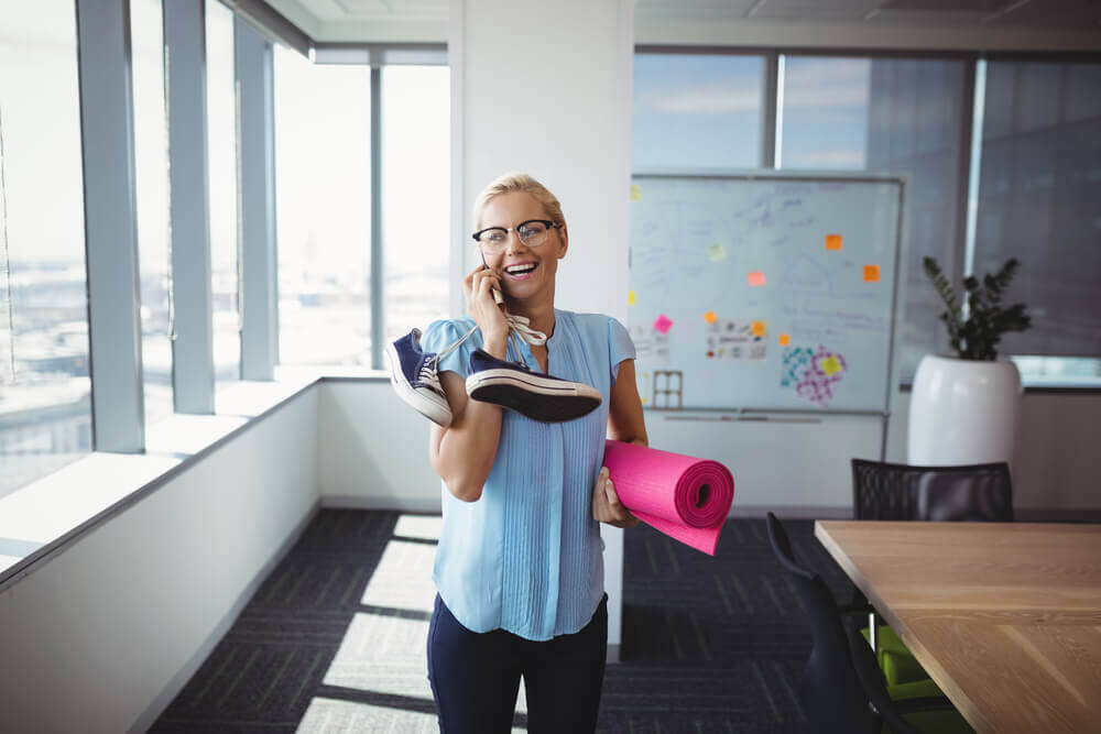 Woman on phone in office holding gym gear