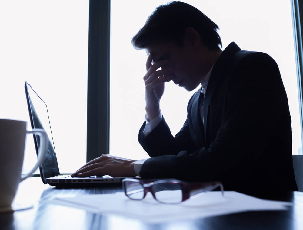 Man stressed at work desk