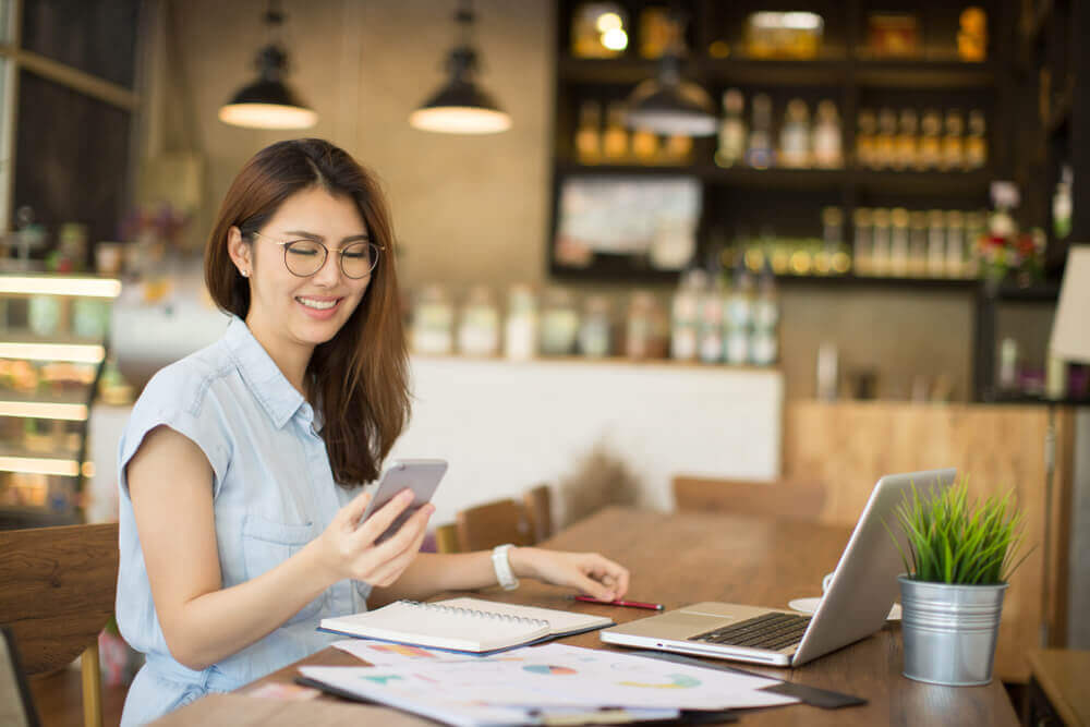 Woman in cafe working with laptop and looking at phone