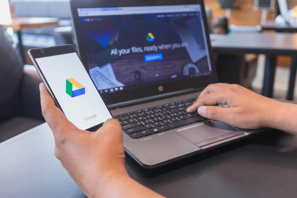 Hand holding phone with Google Drive app and Google Drive open on laptop